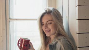 Menina feliz nova com sms da leitura do sorriso do smartphone que senta-se perto da janela panaramic Um louro bonito é video estoque