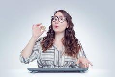 A menina feliz nova com vidros no computador realiza em seu bitcoin da mão Conceito do dinheiro de Digitas foto de stock