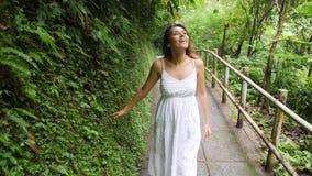 Menina feliz nova da raça misturada no vestido branco que anda na floresta da selva, olhando ao redor e tocando com as folhas tro vídeos de arquivo