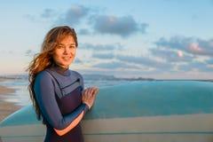 Menina feliz nova da ressaca com cabelo e a prancha longos na praia no por do sol ou no nascer do sol Surfista e oceano imagens de stock