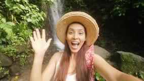 Menina feliz nova do Blogger do turista da raça misturada no vestido e em Straw Hat Making Selfie Video brancos que usa o telefon video estoque