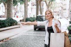 A menina feliz nova do moderno com sacos de compras trava um táxi no fotografia de stock royalty free