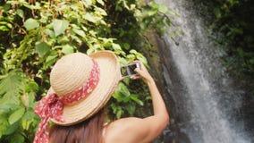 Menina feliz nova do turista no vestido e em Straw Hat Making Photos brancos da cachoeira de surpresa da selva usando o telefone  filme