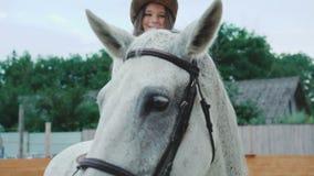 A menina feliz nova levanta em um cavalo consideravelmente branco na área 4K video estoque