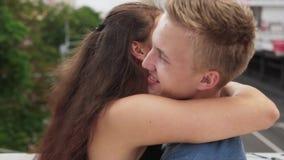 A menina feliz nova no amor abraça delicadamente seu noivo no dia de verão na cidade filme
