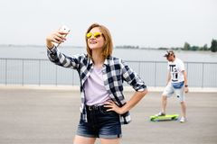 Menina feliz nova no moderno que faz o selfie no telefone fotos de stock