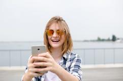 Menina feliz nova no moderno que faz o selfie no telefone fotografia de stock royalty free