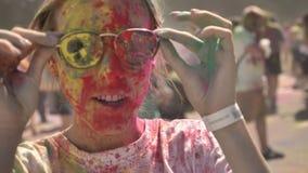 A menina feliz nova no pó colorido veste óculos de sol e começa-os rir no festival do holi no dia no verão, cor filme