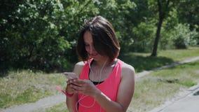 Menina feliz nova nos fones de ouvido que anda no parque A mulher atrativa recebeu a mensagem ao smartphone Menina caucasiano que filme
