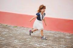 Menina feliz nova que corre afastado Imagens de Stock
