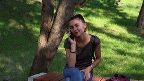 Menina feliz nova que fala no telefone, sorrindo e tocando em seu cabelo, sentando-se em um banco de parque vídeos de arquivo
