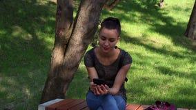 Menina feliz nova que fala no telefone, sorrindo e tocando em seu cabelo, sentando-se em um banco de parque video estoque