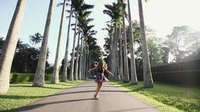 Menina feliz nova que gira ao redor com mãos de espalhamento na plantação do coco Mulher do turista que dança perto das palmeiras filme