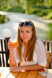 Menina feliz nova que senta-se no terraço com vidro do suco Fotos de Stock