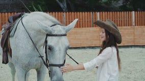 Menina feliz nova que sorri e que acaricia seu cavalo consideravelmente branco na área 4K vídeos de arquivo