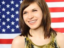 Menina feliz oposto a uma bandeira americana imagens de stock royalty free