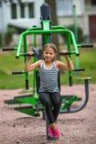 A menina feliz pequena é contratada no equipamento da aptidão do esporte exterior Fotos de Stock