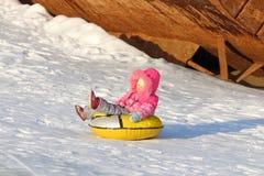 A menina feliz pequena desliza no snowtube Imagens de Stock Royalty Free