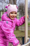 A menina feliz pequena está jogando no campo de jogos da criança Foto de Stock Royalty Free