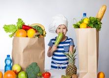 Menina feliz pequena no chapéu do cozinheiro chefe com os sacos grandes da emoção humana positiva das frutas e legumes, sentiment fotos de stock