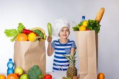 Menina feliz pequena no chapéu do cozinheiro chefe com os sacos grandes da emoção humana positiva das frutas e legumes, sentiment imagens de stock