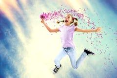 Menina feliz pequena que guarda flores ao saltar foto de stock royalty free