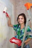 A menina feliz pinta a parede com rolo Imagem de Stock