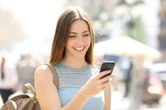 Menina feliz que anda na rua que verifica o telefone fotografia de stock