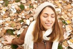 Menina feliz que aprecia nas folhas imagem de stock royalty free