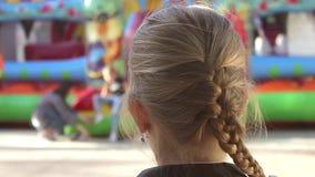 Menina feliz que aprecia um passeio no carrossel Criança bonito da criança que tem o divertimento no funfair Família com crianças filme