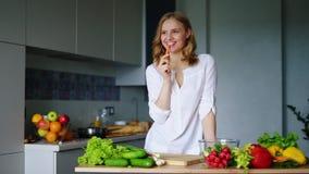 Menina feliz que come a cenoura na cozinha Comer saudável Alimento do vegetariano video estoque