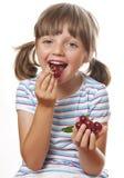 Menina feliz que come cerejas Fotografia de Stock Royalty Free