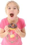 Menina feliz que come a filhós do chocolate Fotos de Stock