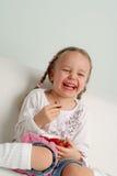 Menina feliz que come a morango Fotografia de Stock Royalty Free