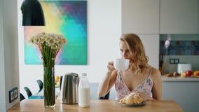 Menina feliz que come o café da manhã na cozinha em casa Mulher caucasiano bonita video estoque