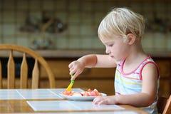 Menina feliz que come a salada saudável dentro fotografia de stock royalty free