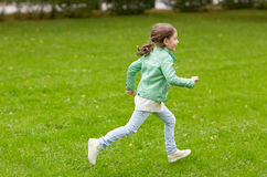 Menina feliz que corre no campo verde do verão Foto de Stock Royalty Free