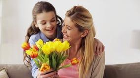 Menina feliz que dá flores para serir de mãe em casa vídeos de arquivo