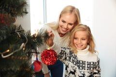 Menina feliz que decora a árvore de Natal com sua mãe em h fotografia de stock