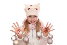Menina feliz que demonstra os símbolos do Natal pintados em suas mãos Papai Noel e rena Imagem de Stock Royalty Free