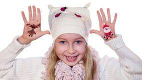 Menina feliz que demonstra símbolos pintados do Natal em suas mãos Santa e rena video estoque