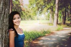 Menina feliz que encontra-se em uma árvore Fotos de Stock