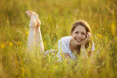 Menina feliz que encontra-se na grama Fotos de Stock Royalty Free