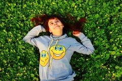 Menina feliz que encontra-se na grama Imagem de Stock Royalty Free