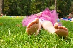 Menina feliz que encontra-se na grama verde foto de stock royalty free