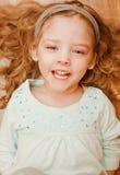 Menina feliz que encontra-se no assoalho Fotos de Stock