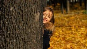 Menina feliz que esconde atrás da árvore video estoque