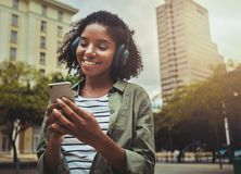 Menina feliz que escuta a música que consulta o índice esperto do telefone imagens de stock
