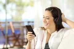 Menina feliz que escuta a música em um apartamento da praia Foto de Stock Royalty Free
