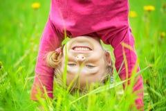 Menina feliz que está de cabeça para baixo na grama no parque do verão Fotografia de Stock